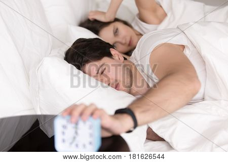 Couple waking up unrefreshed by alarm clock lying in bed on monday morning, young sleepy man trying to turn the alarm off, woman feeling bad, having a headache, drinking too much or sleeping badly