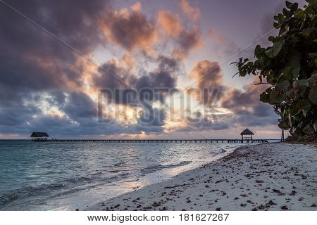 Clouds obscure the sun as it rises over the white sandy beach of Cayo Guillermo in Cuba early one morning.