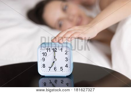 Rested happy woman reaching clock button to turn off daily alarm signal and wake up. Young couple in bed being woken up in the morning. Focus on hand with clock on the table. Wake-up time