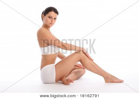 Beautiful healthy young woman wearing white sports underwear sitting on floor with one knee raised against white background showing off fit body and long legs. poster