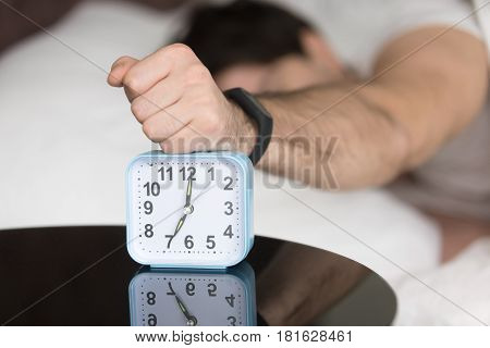 Annoyed sleepy man turning off alarm, hitting button on the clock by his fist after sleepless night, angry and frustrate sleeper feeling not rested and tired, lying in bed and wanting to sleep more