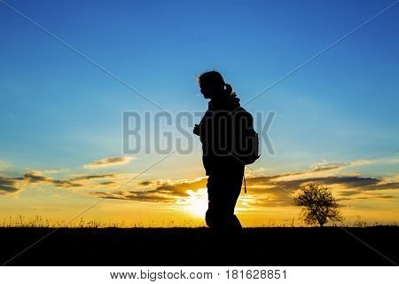 Silhoutte Of A Woman Hiker Over Sunset Sky