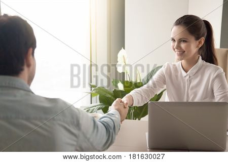 Young cheerful businesswoman and a man handshaking sitting at the office table, arriving for a job interview, greeting a business partner before negotiations, rear view of a man