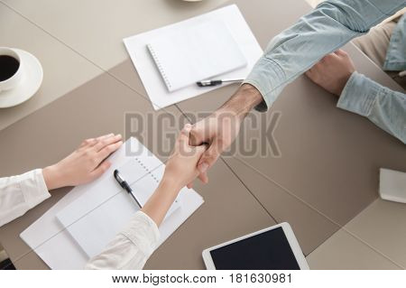 Top view close up of male and female hands shaking over the table, planning strong business working relationships, showing respect. Successful deal, greeting and partnership concept
