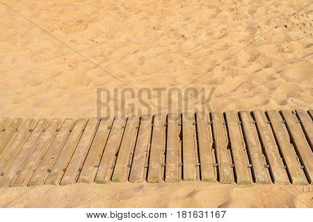 natural background sandy beach and wooden walking path or footpath closeup