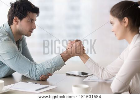 Side view on young man and woman armwrestling, desiring to outperform the competitor, companies struggling for leadership, feminism and equal rights of women in business or society poster