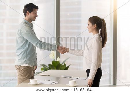 Friendly male executive standing at the office table shaking hands and congratulating recently hired young female manager, greeting or finishing meeting, closing deal or making agreement