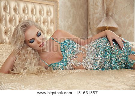 Beautiful Alluring Sexy Blond Woman Portrait In Fashion Decollete Dress Lying On Modern Bed In Luxur