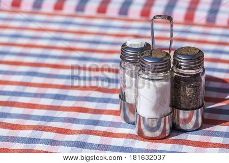 Salt pepper and toothpick set over an outdoor restaurant table in Italy