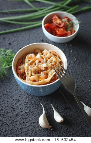 Tagliatelle pasta with shrimps and tomato sauce on dark background. Fresh italian cuisine.