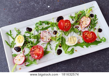 Fresh radish, cherry tomato, quail egg, ruccola with balsamic glaze on a white plate. Mediterranean lifestyle. Healthy food