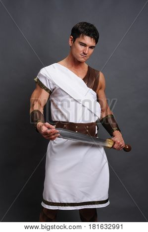 The distinguished warrior is holding a sword.