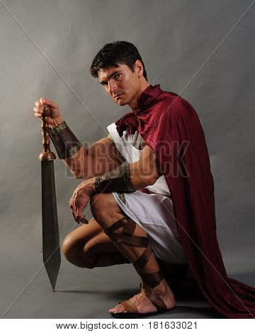 The sexy king is kneeling down with a sword.
