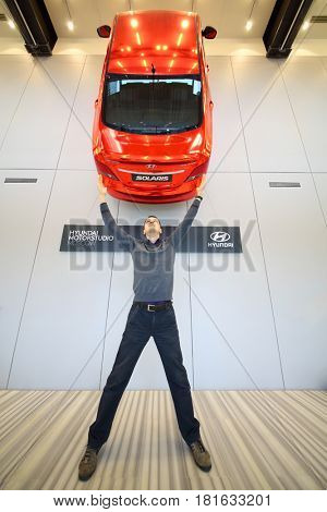 MOSCOW - APR 16, 2016: Red Hyundai Solaris on wall and man stands under it (with model release) in Hyundai Motorstudio. Hyundai produces not only cars, but also its own collection of furniture