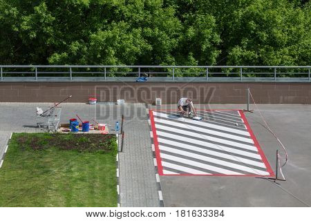 MOSCOW, MAY 28, 2016: Man makes marking on parking for fire equipment in Elk island residential complex