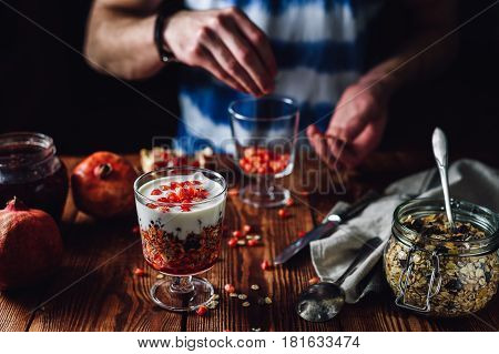 Dessert with Pomegranate and Man Prepare New Portion on Backdrop. Series on Prepare Healthy Dessert with Pomegranate Granola Cream and Jam