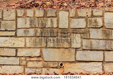 Texture of the stone wall in the autumn park with dry leaves