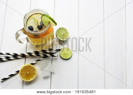 refreshing water with lemon and orange with tubes in a jar on a white wooden table