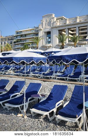 Many blue loungers and parasols on beach with pebbles in Cannes, France