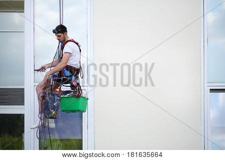Young man hangs on safety cable and cleans window of high building