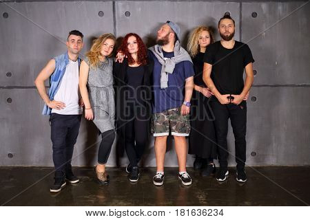 Six young fashionable people (three men, three women) pose in studio