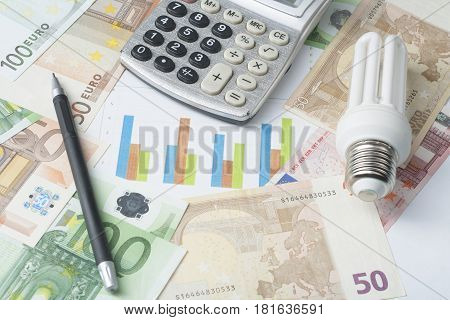 Energy saving lamp, chart and calculator on money background, Eco energy saving light bulb, comparison of energy saving lamps and incandescent lamps