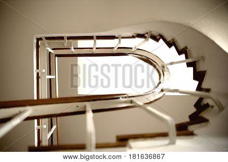 The underview of a staircase with a spiral staircase and railings.