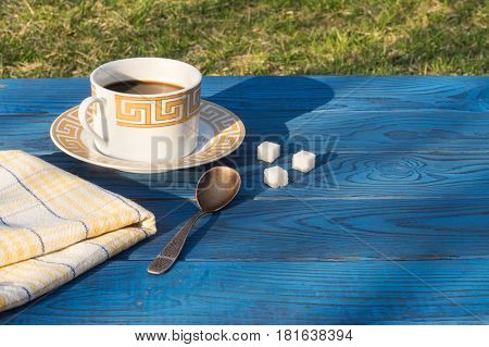 Coffee cup and shugar on a table of blue boards. Behind - green grass