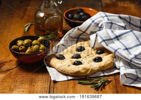 Traditional Italian Focaccia with olives and rosemary with olive oil on wooden table