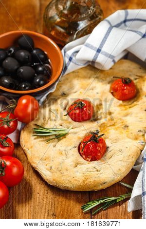 Traditional Italian Focaccia with tomatoes and rosemary with olive oil on wooden table