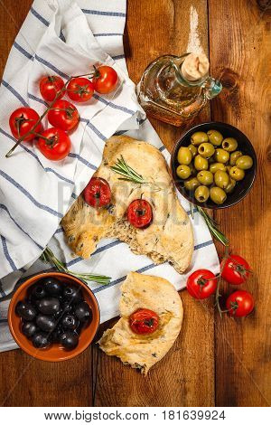 Traditional Italian Focaccia with tomatoes and rosemary with olive oil on wooden table. Top view