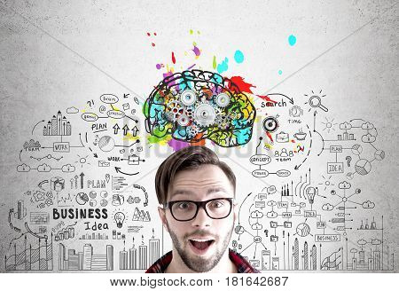 Portrait of an excited young man wearing glasses and standing near a concrete wall with a brain sketch with cogs and a business plan drawn on it.