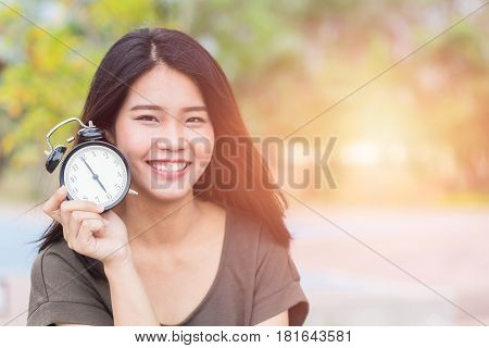 Thai Asian women show and point her face aside with clock Time reverse back to baby skin concept.