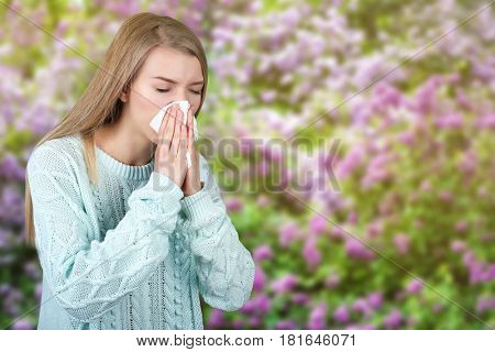 Seasonal allergy. Young woman with tissue outdoor