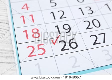 Check mark in calendar on date of 26th, close up