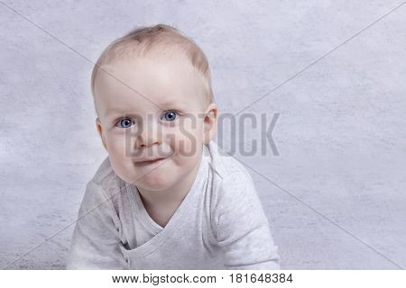 Adorable baby boy learning to crawl and playing. Cute laughing child crawling on a bed. Copy space