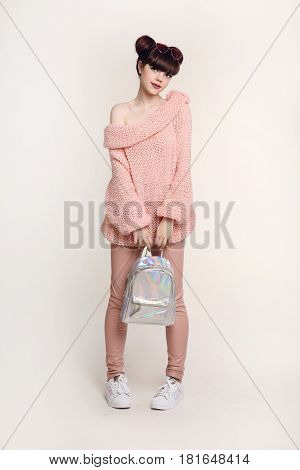 Fashion Teen Look Style. Fashionable Young Girl Wears In Wool Sweater And Leather Pants, Holding Bac