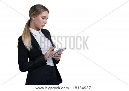 Isolated portrait of a serious blond woman wearing a black and white business suit writing in her small notebook.