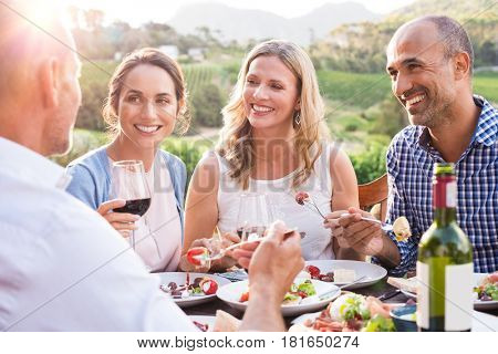 Group of mature people eating together in a vineyard in a summer day. Happy woman sipping wine while talking to friends during a lunch in a winery. Senior couple having dinner with wine at sunset.