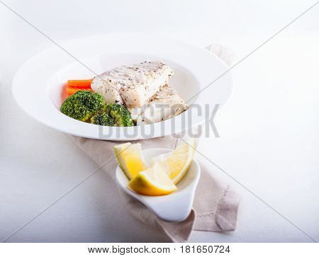 Healthy lunch with cod and steamed vegetables