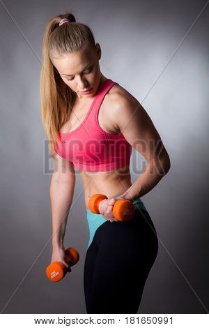 portrait of young sport girl with dumbbells and makeup on gray background
