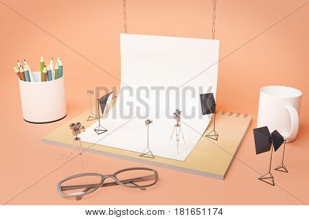 Creative tiny photo studio made out of supplies: white paper coffee cup pencils glasses and other items on peachy background. Closeup 3D Rendering