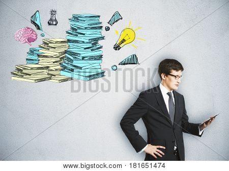 Handsome young businessman using tablet on concrete background with drawn paperwork stacks. Workload concept
