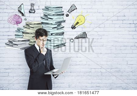 Businessperson using laptop on white brick background with drawn paperwork pile. Workload concept