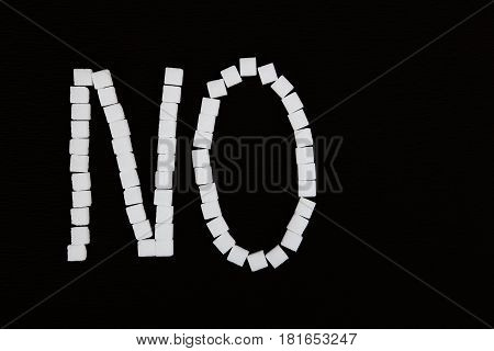 Word no made from white sugar cubes. Isolated on a black background.