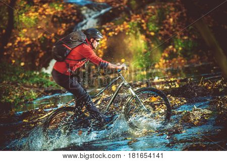 Extreme Bike Ride River Crossing in the Scenic Forest. Caucasian Biker on the Mountain Bike Fast Ride.