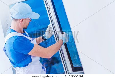 Window Replacement Installation by Professional Caucasian Construction Worker. Home Building or Remodeling Photo Concept.