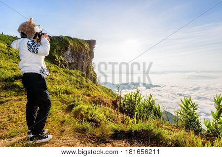 Asian hiker woman with digital camera photographing beautiful natural landscape of sky clouds and fog during sunrise in winter on mountain at Phu Chi Fa Forest Park Chiang Rai Province Thailand