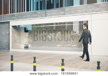Side view of young man walking by glass shopfront during daytime. Ad concept. Mock up 3D Rendering