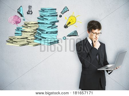 Handsome young businessman using laptop on concrete background with drawn paperwork stacks. Workload concept
